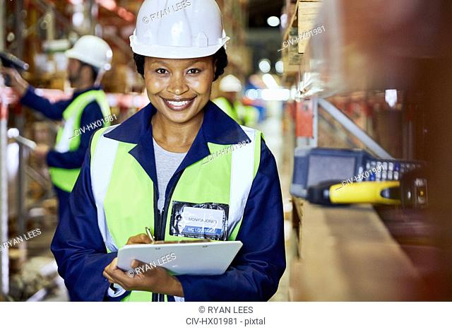 Portrait smiling female worker with clipboard in distribution warehouse