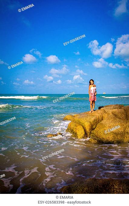 Young sexy woman stands on stones at water. Koh Samui