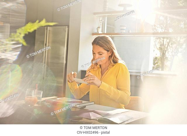 Woman with camera phone photographing art at sunny kitchen table