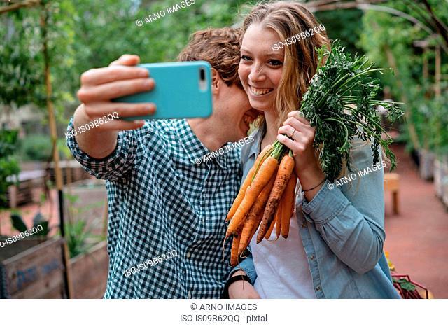 Couple in garden with carrots, taking selfie
