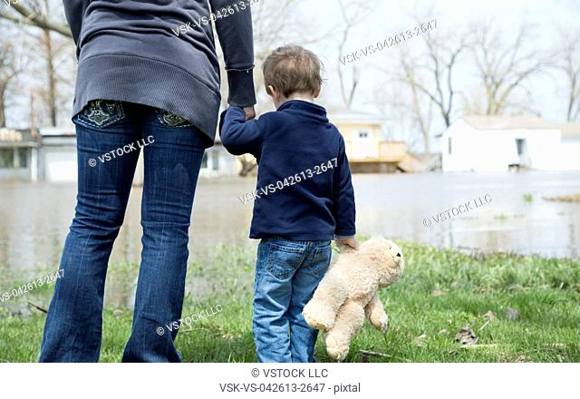 Mother with son standing in flooded town