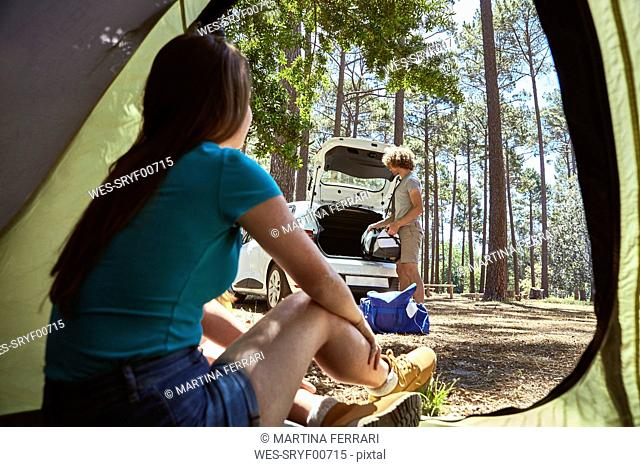 Young woman sitting in a tent watching her boyfriend packing the car