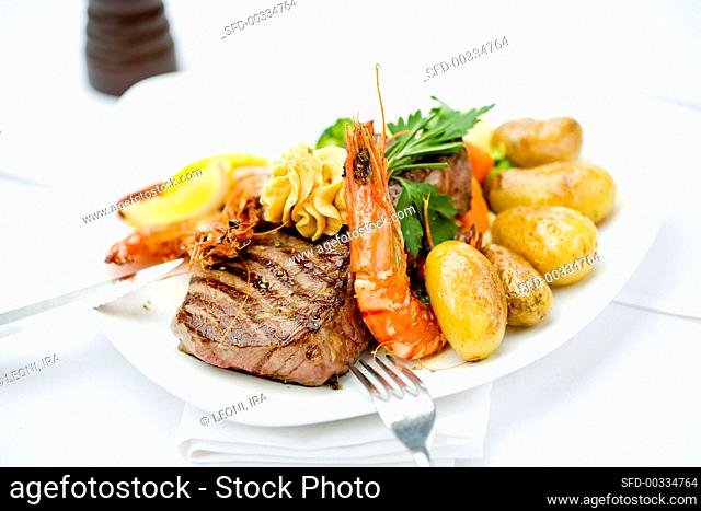 Rump steak with king prawns and potatoes