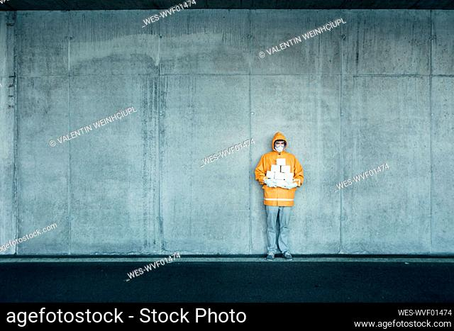 Portrait of man wearing protective clothing holding toilet rolls