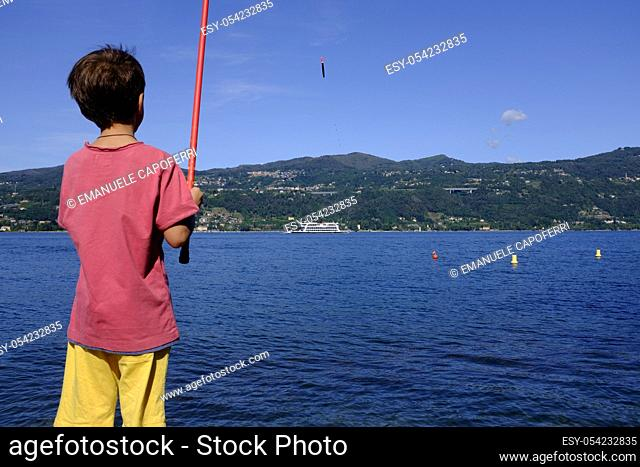 Child fishing, Lake Maggiore, Ranco, Lombardy, Italy