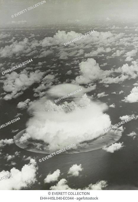 The BAKER test of Operation Crossroads, July 25, 1946. The fireball and water column emerge from the dome of condensation cloud less than two seconds after the...