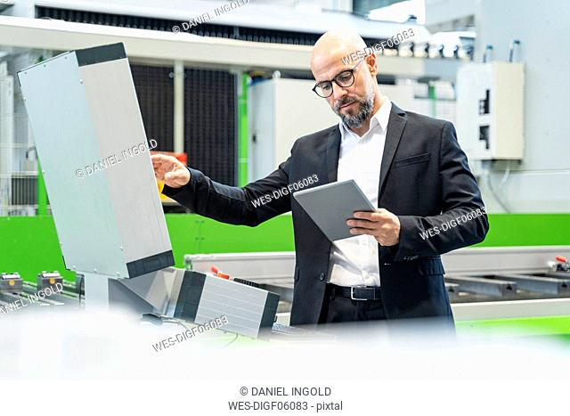 Businessman using tablet at machine in factory