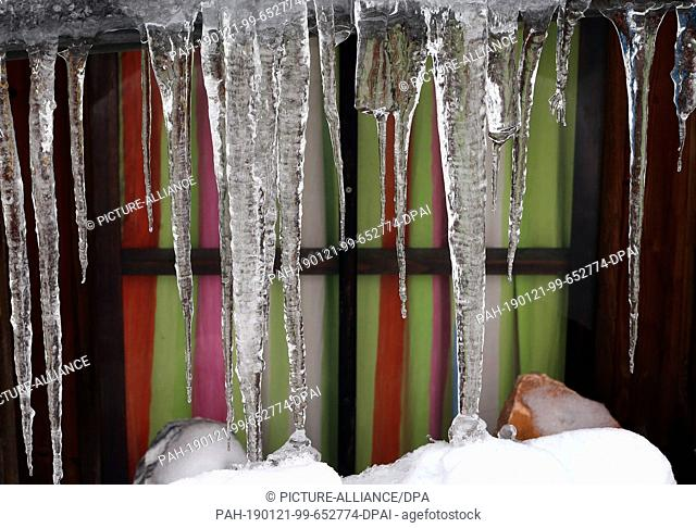 21 January 2019, Bavaria, Oberjoch: A curtain of icicles hangs in front of the window of a house. Photo: Karl-Josef Hildenbrand/dpa