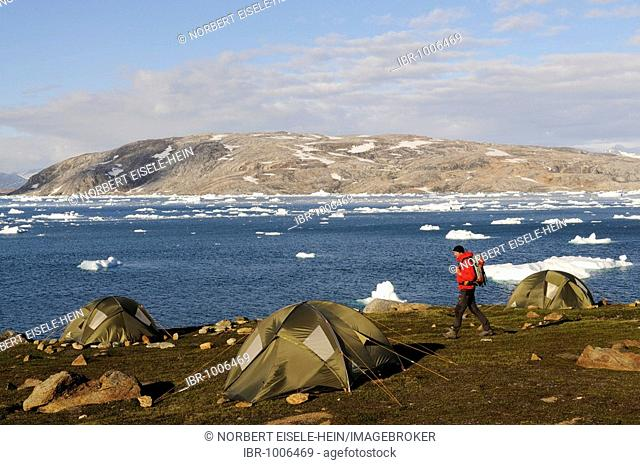 Trekker and tents, camping in the Johan-Petersen-Fjord, East Greenland, Greenland