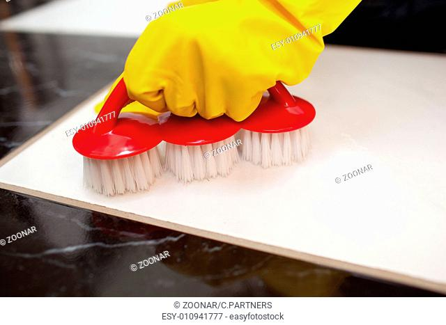Close-up of a person cleaning a bathroom's floor