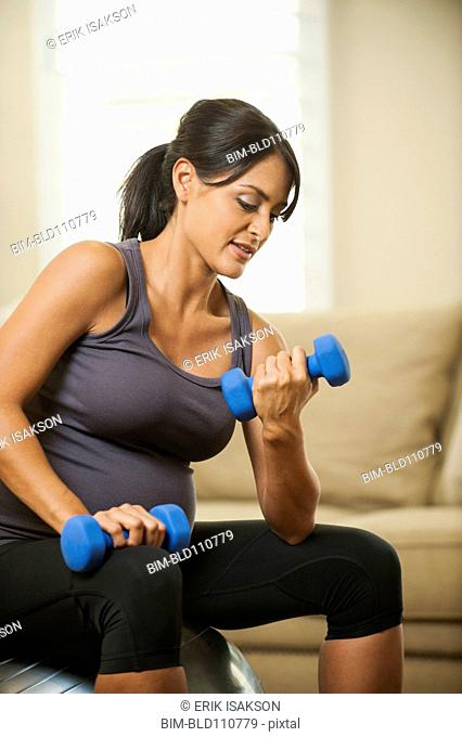 Pregnant Hispanic woman lifting weights