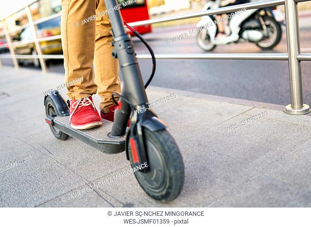 Man with electric scooter in the city, partial view