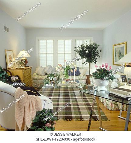 LIVING ROOM - Plaid rug. White walls, wood floor, windows with white shutters, ficus tree, floral sofas glass tables, gold framed artwork, tulips vased