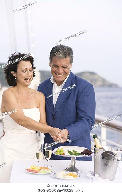 Newlywed couple cutting wedding cake on boat deck
