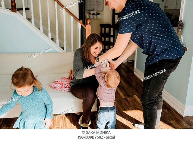 Mid adult couple with baby boy and female toddler in living room