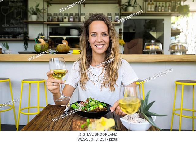 Portrait of smiling woman holding glass of wine in a cafe