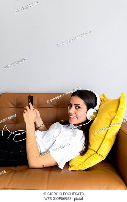 Young woman lying on the couch at home with smartphone and headphones