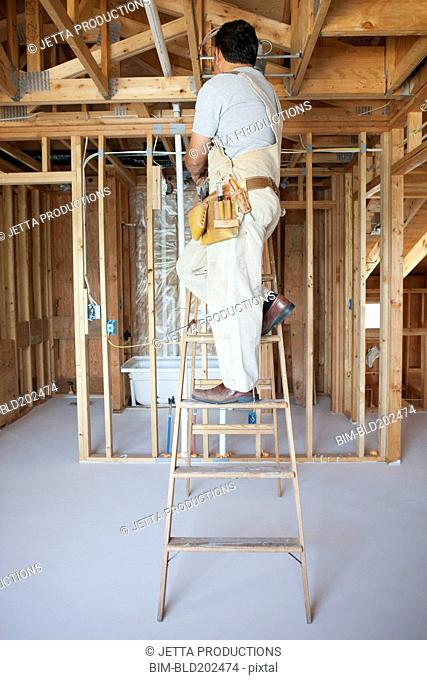 Hispanic construction worker on ladder in unfinished room