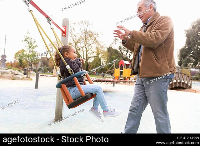 Grandfather pushing granddaughter on playground swing