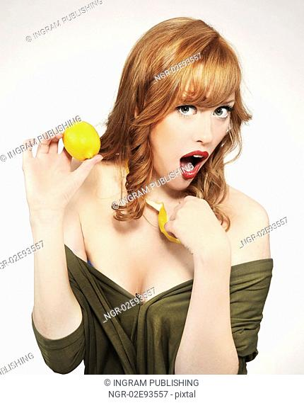 Young woman holding a lemon