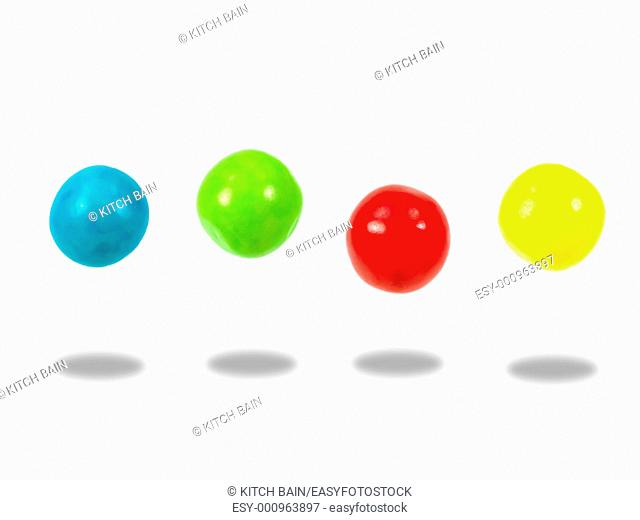 Large colored gumballs set against a white background