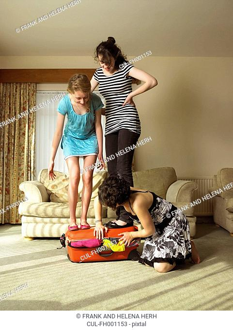 Three females trying to close suitcase