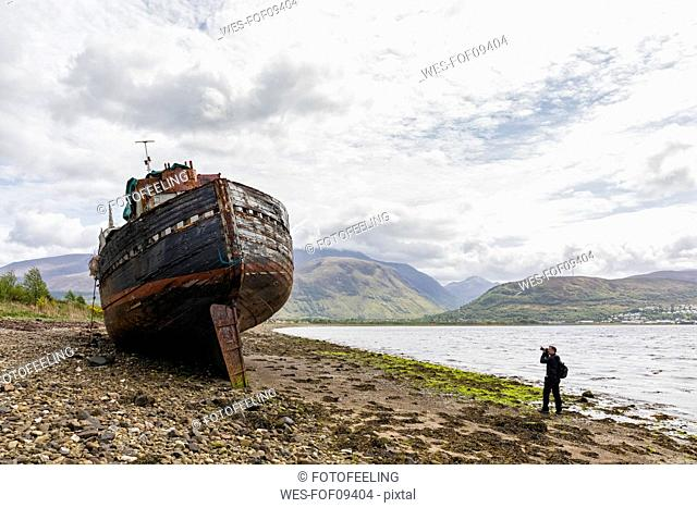 UK, Scotland, Highland, photographer taking picture of ship wreck at the beach of Corpach