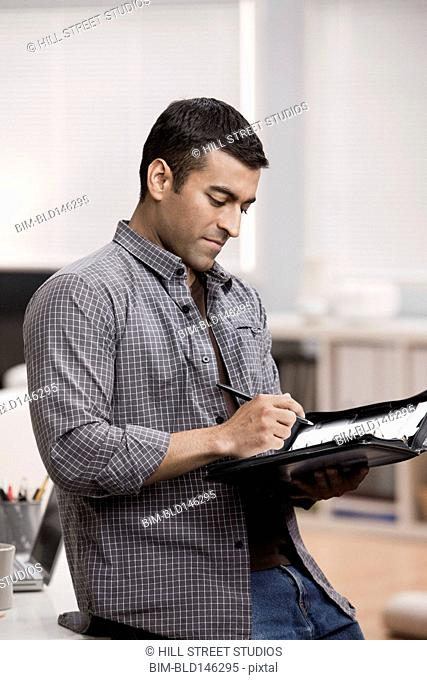 Hispanic man writing in planner in home office