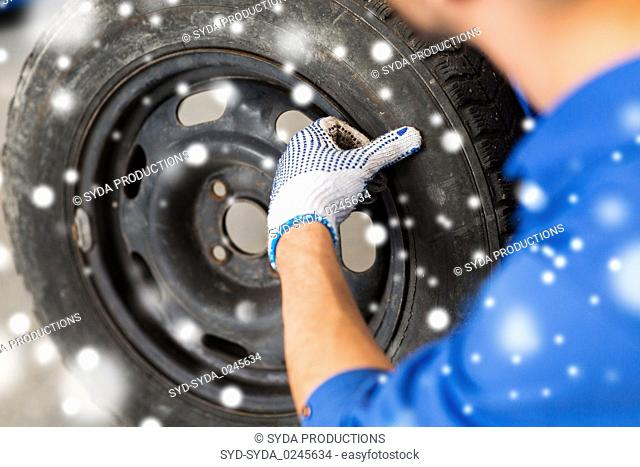 close up of auto mechanic with car tire