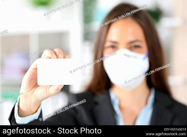 Front view of executive woman hand showing blank credit card avoiding covid-19 with mask at office