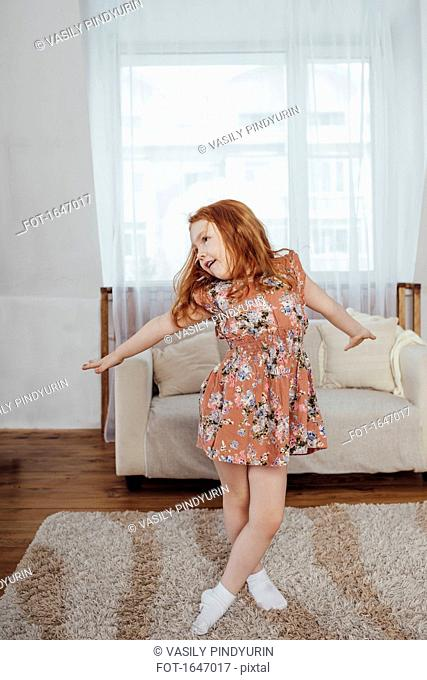 Happy girl with arms outstretched dancing on carpet at home