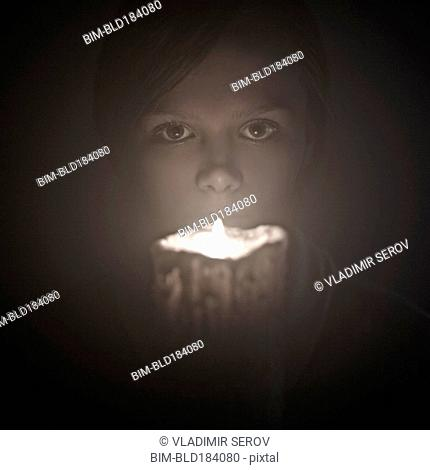 Caucasian woman holding candle near face