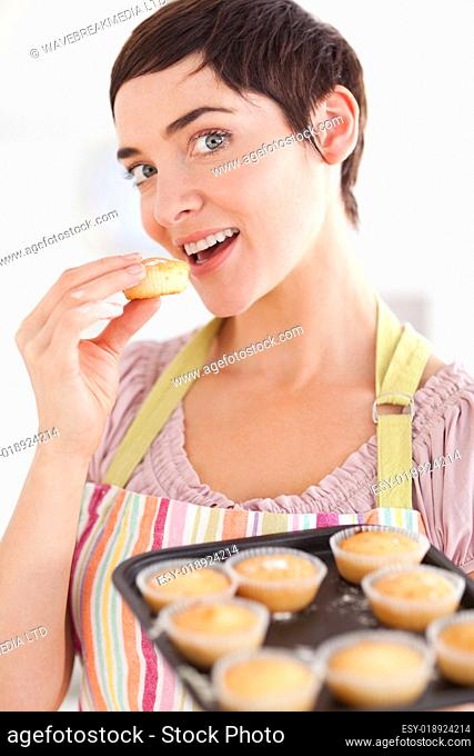 Charming brunette woman showing muffins while eating one