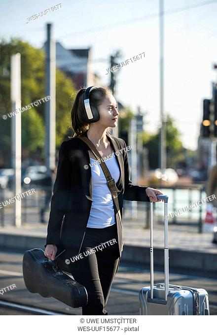 Young woman with headphones, suitcase and violin case at tram station