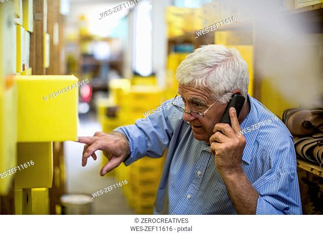 Senior man on the phone in warehouse with shoe boxes