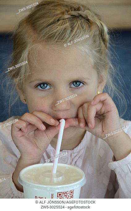 Blond girl, 4 years old, drinking cola with drinking straw in Ystad, Scania, Sweden