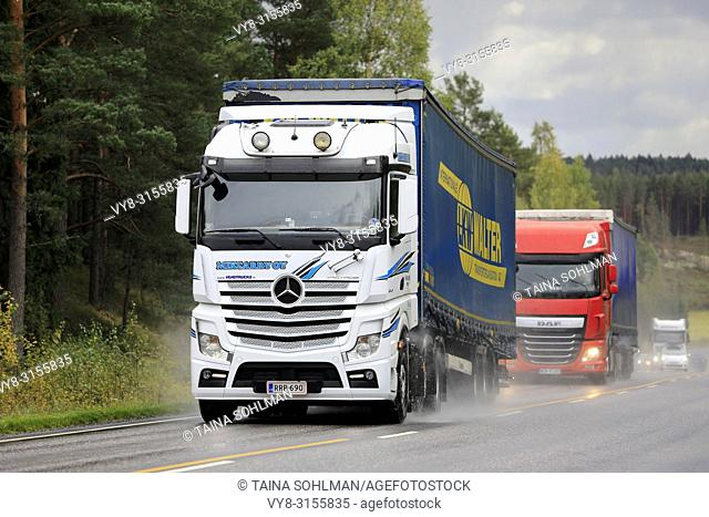 Salo, Finland - September 28, 2018: White Mercedes-Benz and red DAF freight semi truck traffic on wet road on rainy autumn day in South of Finland