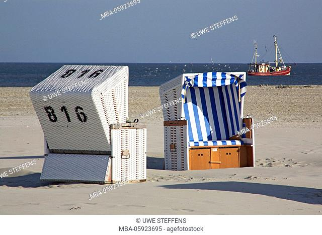 Morning hour with shrimp boat and beach chairs on the beach of Ording