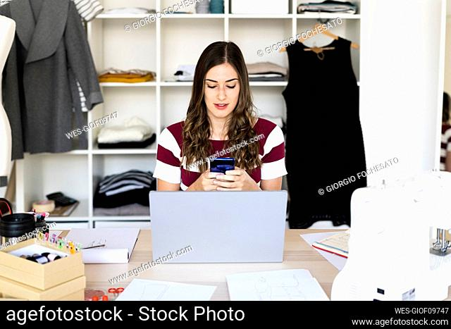 Female fashion designer using smart phone while sitting with laptop in studio