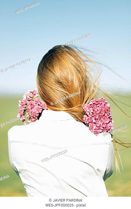 Rear view of woman with flowers outdoors