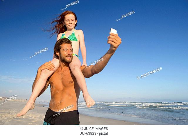 Father, with daughter sitting on shoulders, taking selfie on sunny beach