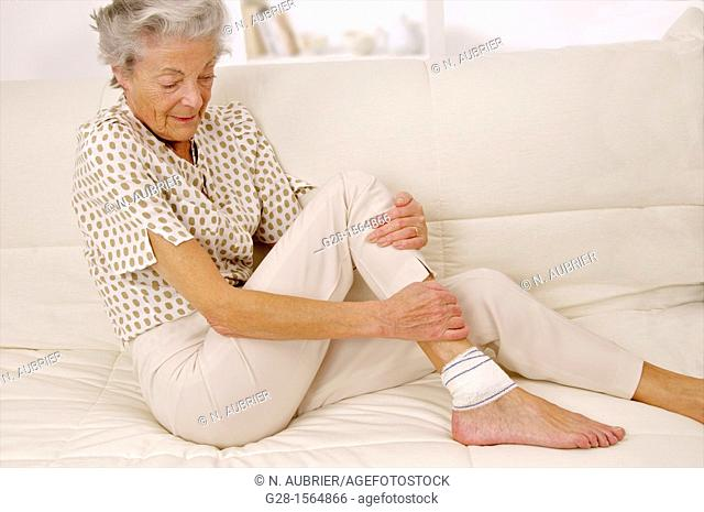 Senior woman with a bandaged ankle sitting on a sofa