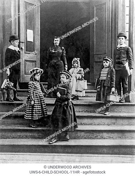 United States: c. 1880.Children arriving at school with their books straps and wicker lunch baskets