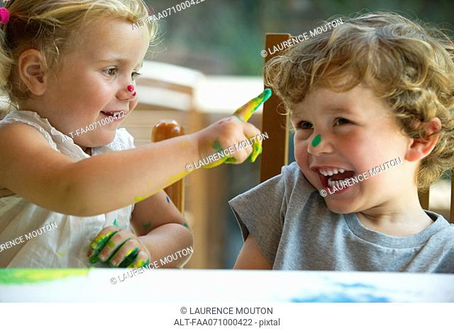 Little girl wiping paint on her brother's nose