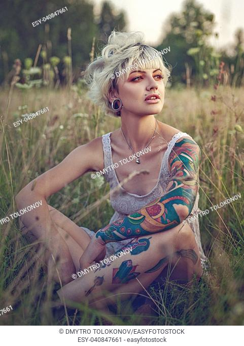 Sharp looking blonde. Summertime female portrait. Young adult woman with tattos. 08 August 2018, Kiev, Ukraine