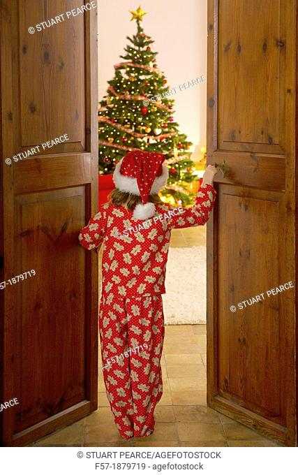 Young girl opening the living room doors at Christmas time