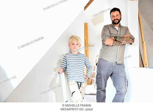 Portrait of confident father and son working on loft conversion