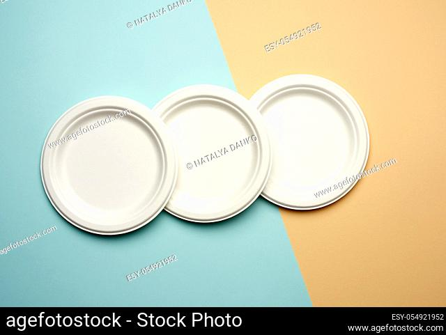 stack of white paper disposable plates on a beige-blue background, top view. The concept of rejection of plastic, environmental conservation