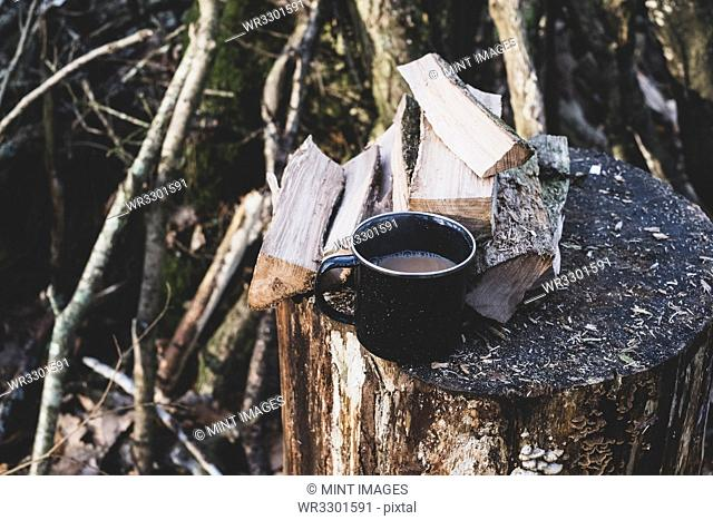 High angle close up of mug of tea and wooden logs on chopping block