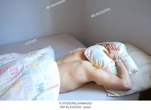 Young man sleeping with head under pillow in bed